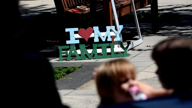 """A family is seen silhouetted in front of a sign that reads """"I 'heart' my family"""" during the Reunification Day celebration at the Hall of Justice on Friday, June 24, 2016 . The Michigan Supreme Court, Michigan Department of Health & Human Services, and others celebrated Reunification Month the event which highlighted families that have been involved with foster but have been reunited."""