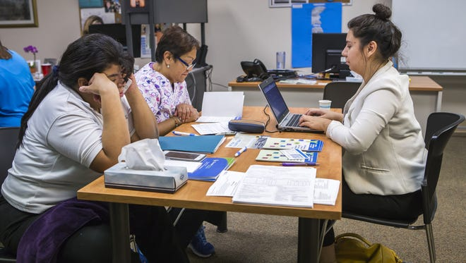 Yadira Alonso (right), a certified application counselor, helps prospective healthcare marketplace customers find a suitable insurance plan at the Westside Family Healthcare office in Bear last year.