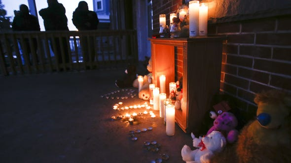 People gather at a makeshift memorial on the porch