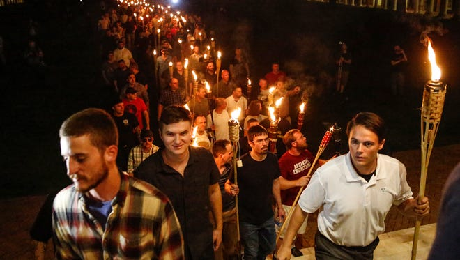 Peter Cetanovic, right, and other white nationalists march with torches through the UVA campus in Charlottesville on Friday, August 11, 2017.
