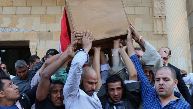 People carry the coffin of police captain Ahmed Fayez, who was killed in a gun battle which began Friday, in al-Wahat al-Bahriya area in Giza province, about 84 miles southwest of Cairo, during his funeral at Al-Hosary mosque, in Cairo, Egypt, on Oct. 21, 2017.