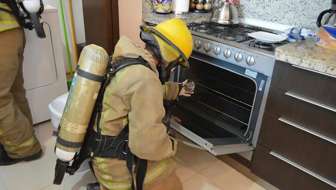 In this undated photo provided by the Quintana Roo Prosecutors Office, a firefighter examines a gas stove in the rented condo where an Iowa couple and their two children died in Tulum, Mexico. Mexican authorities said on Saturday, March 24, 2018 that autopsies indicate the Iowa couple and their two children died from inhaling toxic gas at the rented condo on Mexico's Caribbean coast, but there was no sign of foul play or suicide.