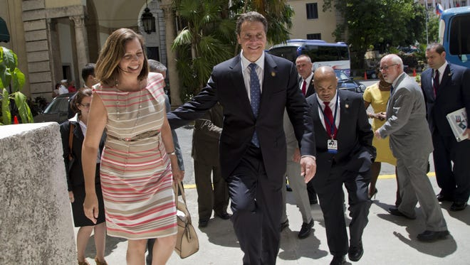New York Gov. Andrew Cuomo, center, and Cuban Foreign Ministry Director for North America Josefina Vidal walk by Nacional Hotel in Havana on April,20, 2015. Cuomo said his government wants to be present in the beginning of the official diplomatic relations between Cuba and the U.S.