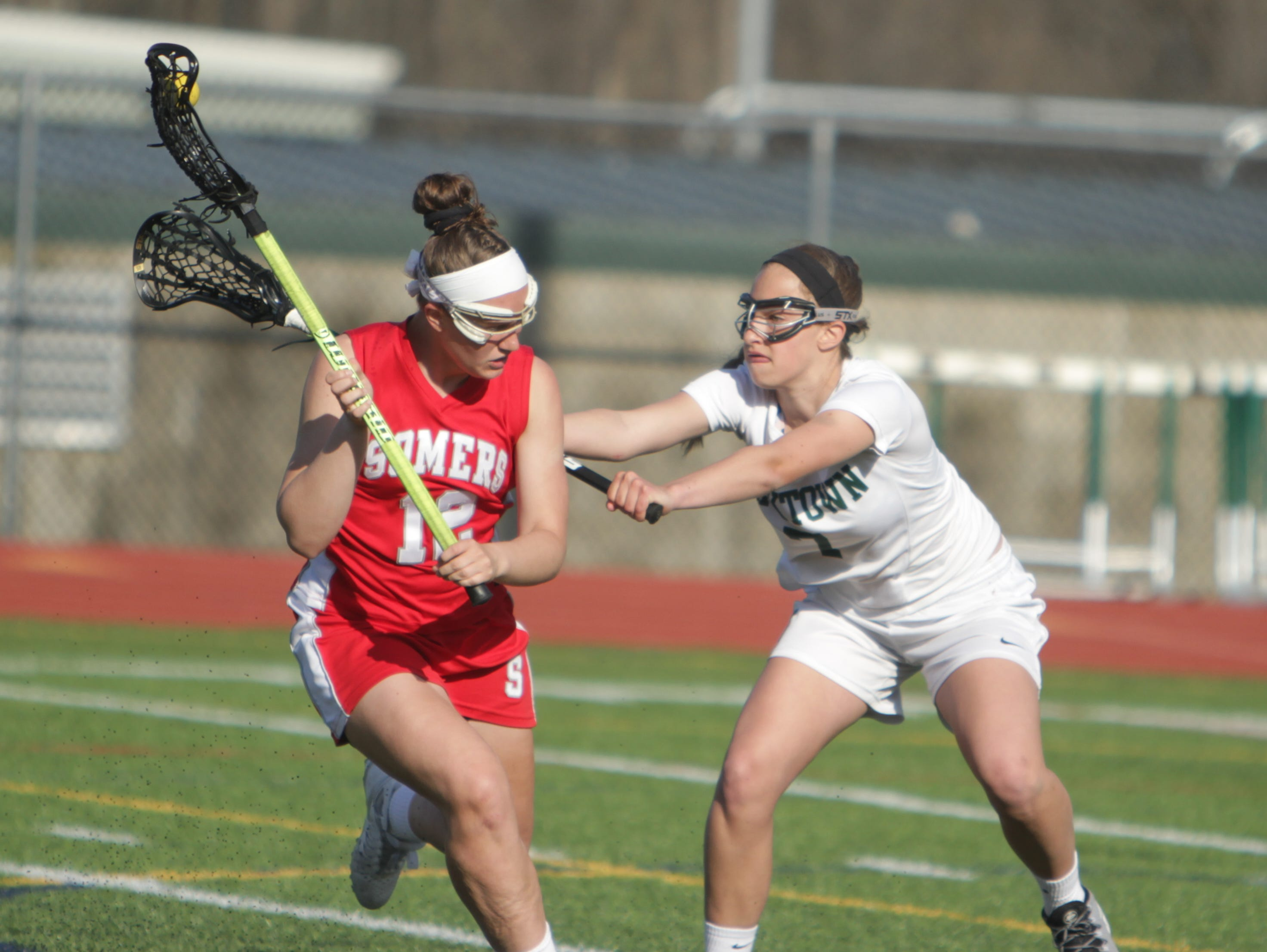 Somers' Livy Rosenzweig is defended by Yorktown's Carli Mager during a Section 1 girls lacrosse game between Yorktown and Somers at Yorktown High School on Thursday, April 21st, 2016. Somers won 11-10.
