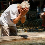 A man spreads water over his face as the temperature felt like around 100 degrees on July 25, 2016, in New York City.