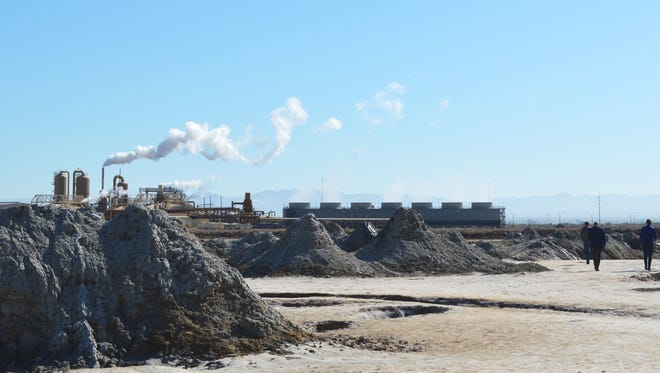 Controlled Thermal Resources executives Rod Colwell, Paul Horsburgh and Jason Czapla (seen at far right) walk past bubbling mud pots by the southern shore of the Salton Sea as EnergySource's Featherstone geothermal plant belches steam in the distance on April 29, 2016.
