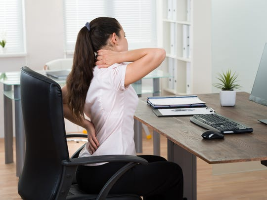 Young Businesswoman Sitting On Chair Having Backpain In Office
