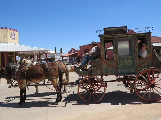 On a stagecoach tour of the town, a visitor pokes her head out of the window. Sights like this are common in Tombstone.