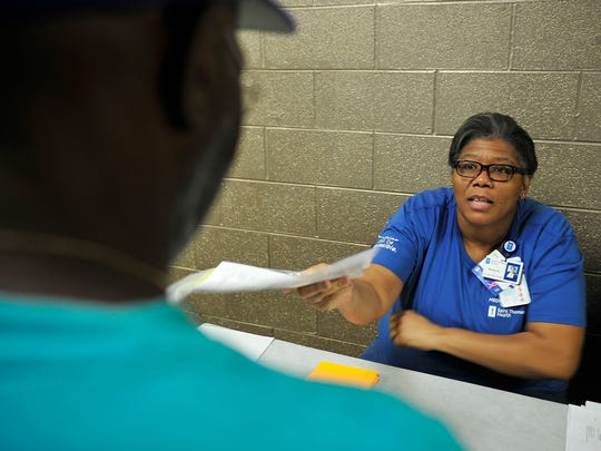 Volunteer Keena Kleckley hands out a document to a