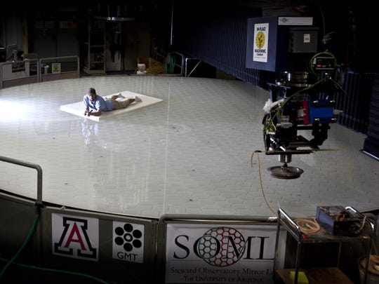 A worker lays on top of the first mirror of the Giant