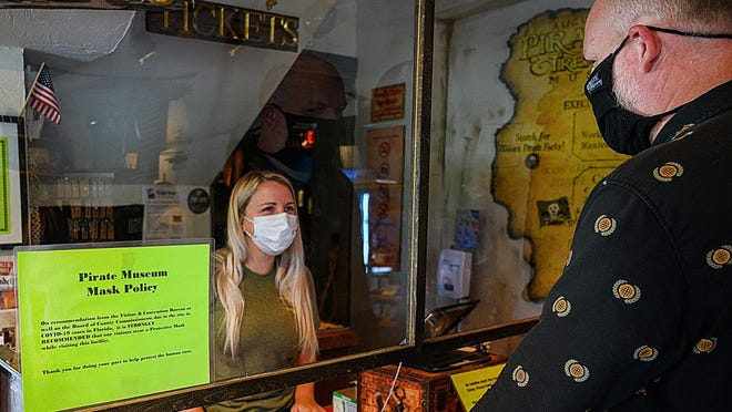 St. Augustine Pirate & Treasure Museum cashier Randi Wells talks to the business' director of communications Zachary Lively in the museum's giftshop on Thursday, June 25, 2020.  The pirate museum requires employees to wear masks and recommended visitors do so as well. On Friday St. Augustine commissioners voted  4-0 Friday to require face coverings indoors, with some exceptions.