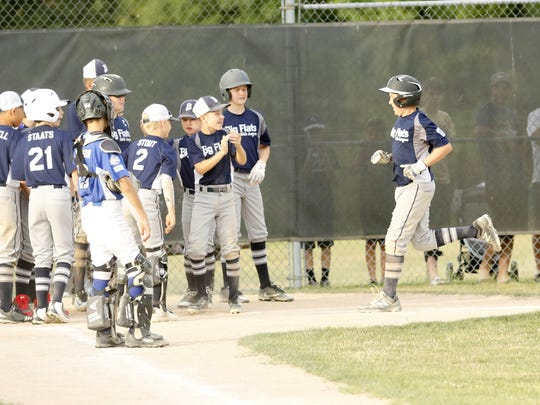 Big Flats players greet Cam Kennedy after his home run in a 13-3 win over Horseheads in the District 6 Little League 11-12 championship game in Painted Post.