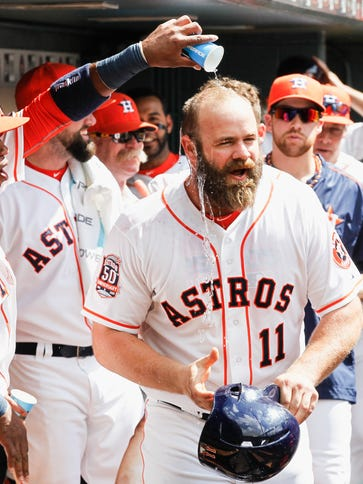 Evan Gattis is doused with water by Luis Valbuena #18