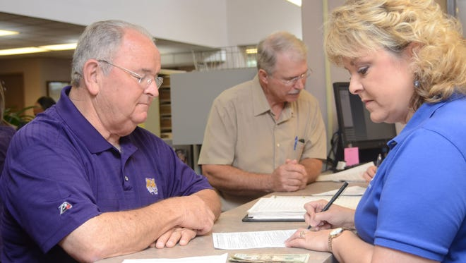 Woodworth Mayor David C. Butler II (left) qualifies Wednesday to run for re-election as Rapides Parish Clerk of Court Robin Hooter looks on Wednesday. Qualifying for local offices in the Nov. 4 primary elections continues through Friday at clerk of court offices throughout Central Louisiana.