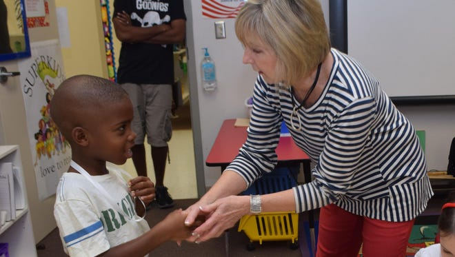 Riley Brown (left) greets his first-grade teacher Ginger Cespiva at Alexandria Country Day School on the first day of the semester Wednesday.