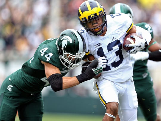 Michigan wide receiver Eddie McDoom is tackled by Michigan State safety Grayson Miller during a game in 2016.