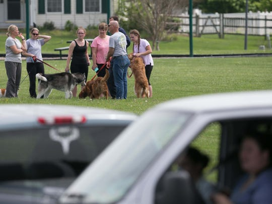 Residents look on at law enforcement from a central park in the Brick Mill Farm neighborhood in Middletown.