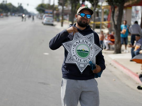 A man holds a Salinas Police magnetic badge before returning it to an officer before the start of El Grito Parade on Sept. 17. A city-commissioned survey is seeking Salinas residents' opinions on the police and its relationship with the community.