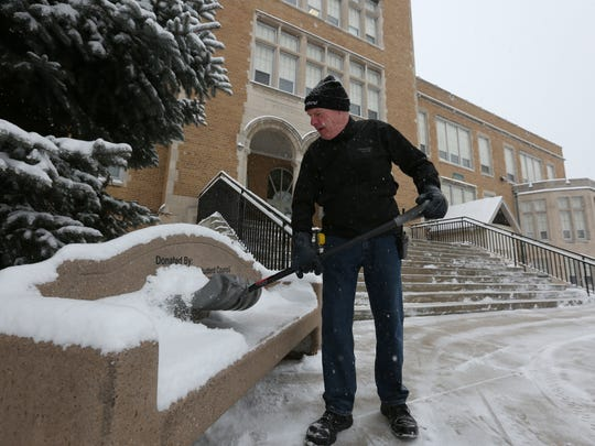 Wilson Junior High School custodian Jack Wanek shovels a bench outside the school Tuesday morning, March 1.