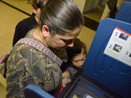 Kera Hart casts her ballot in Williamston's Piercetown precinct while her children look on intently. Shown are Chloe, 2, at bottom; Bailey, 7, just above her; and Jeremiah, 10, behind his mother.