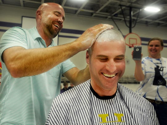Jason Garner applies shaving cream to the head of Thelma Barker Elementary School Principal Ryan Kirkbride, Friday afternoon. Students witnessed their principal have his head shaved as a reward for reaching their fundraising goal for Relay for Life.