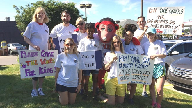 Big siblings of Big Brothers Big Sisters show of their signs from the 2015 fundraiser.