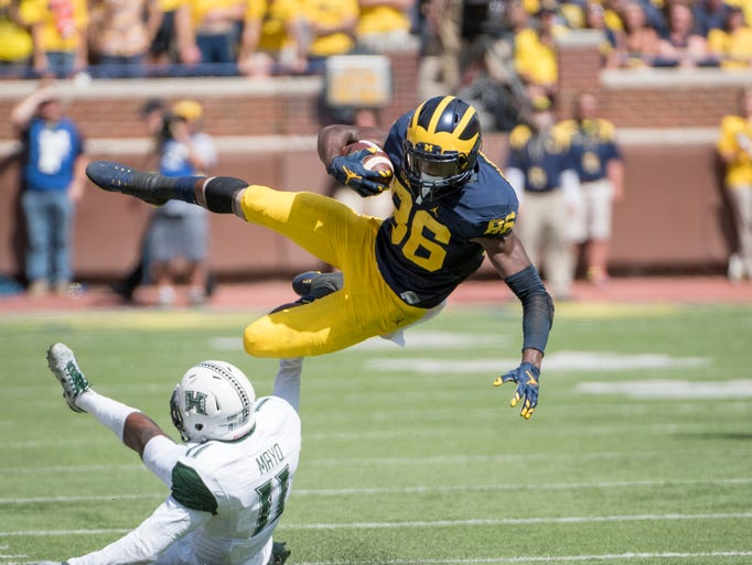 Michigan wide receiver Jehu Chesson leaps over Hawaii