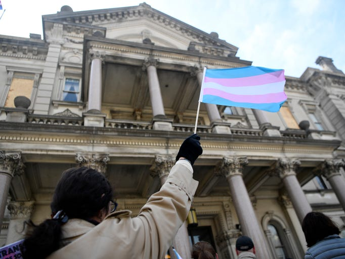 A woman waves a flag representing transgender people
