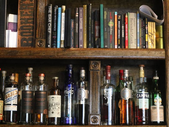 A library of cocktail cookbooks amid liquors at Lucky