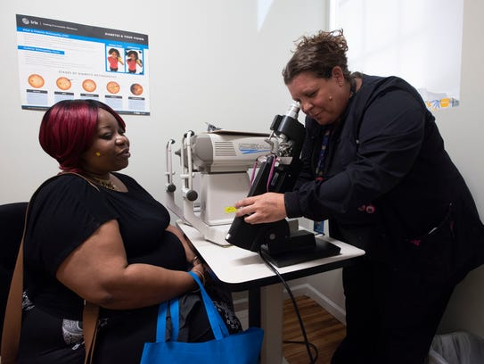 Ophthalmology tech, Wendi Adams, right, gives patient,