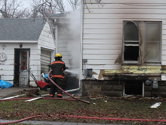 A Grinnell fire firghter hoses down the back of the residence at 503 Park in Grinnell after being called to a house fire early Monday, Nov. 30.
