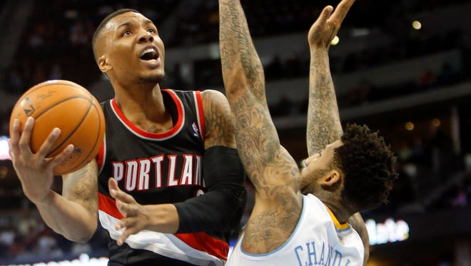 Portland Trail Blazers guard Damian Lillard (0) attempts a layup over Wilson Chandler (21) of the Denver Nuggets at Pepsi Center. The Trail Blazers won 100-95.