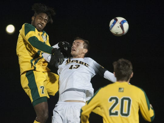 Vermont's Brian Wright (7) leaps over UMBC's Gregg Hauck (13) to head the ball during the America East semifinal playoff game between the UMBC Retrievers and the Vermont Catamounts at Virtue Field on Wednesday night.