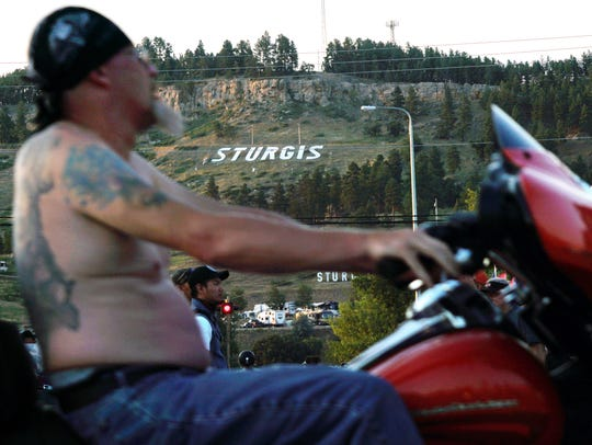 A shirtless rider on Main Street passes the Sturgis