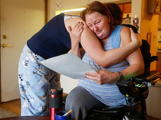 Ilene Montgomery, left, comforts her mother Margaret Montgomery as she looks at a family portrait that includes her daughter Raquel Montgomery. Raquel was murdered on Tuesday, Feb. 13, 2018.