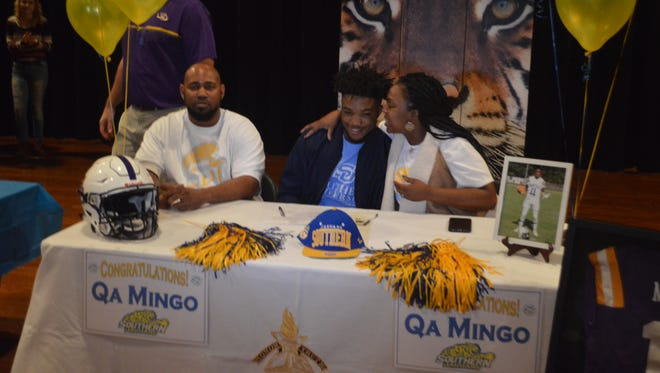 Marksville quarterback Qa Mingo (center) receives a kiss from his mom after signing as a preferred walk-on with Southern Thursday.