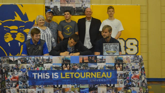 Buckeye senior Tyler Paulk (center) signs with LeTourneau Tuesday.