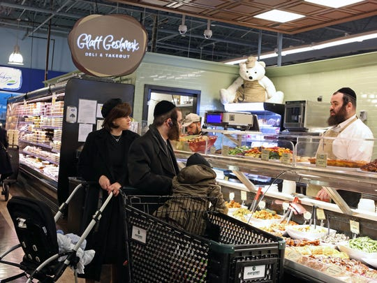 Yidel Spitzer helps a family at the Glatt Geshmak Deli & Takeout section at Evergreen Kosher Market in Monsey, Nov. 24, 2015. This supermarket is considered a game changer when it comes to kosher supermarkets regarding the prepared foods section and a checkout/delivery service.