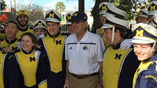 Former U-M football coach Lloyd Carr poses with the Michigan marching band.