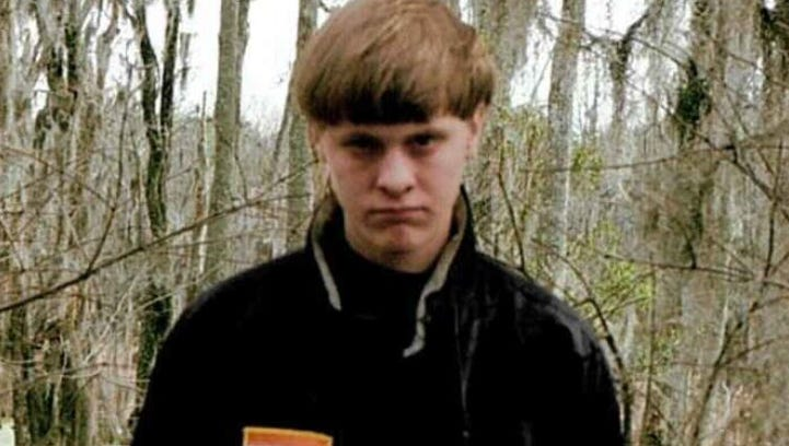 Dylann Roof is pictured in a self-portrait wearing the defunct flag patches of Rhodesia and apartheid South Africa, states that were linked to white supremacy.