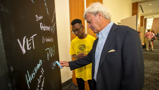 Chuck Ramsey adds his occupation to the chalkboard at Boys & Girls Clubs' annual Stake & Burger event, while Club member Anthony Davis watches.