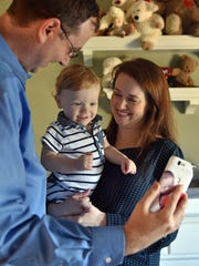 James, left, and Chelsea Lamb play with their 14-month-old son Jay at their home in Brandon Tuesday. Jay was born with a genetic condition that causes benign tumors called tuberous sclerosis. James and Chelsea both work full-time jobs and both have health insurance yet they believe they would not be able to afford their son's medical expenses without the aid of Medicaid.