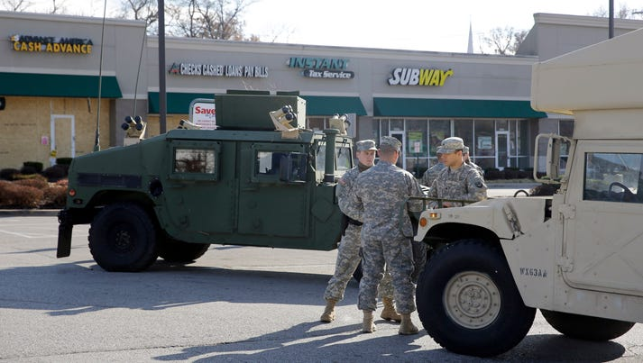 Members of the Missouri National Guard stand in a parking