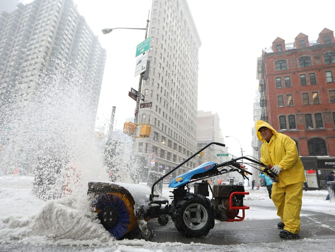 A man clears the sidewalks across from the Flatiron