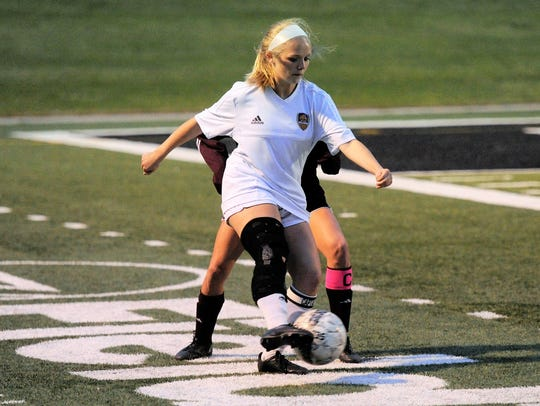 Wylie's Kaleigh Wilson (21) holds off a Brownwood defender