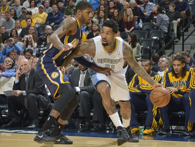 Denver Nuggets small forward Wilson Chandler (21) moves around Indiana Pacers small forward Paul George (24) during the first quarter of an NBA basketball game Saturday, Jan. 25, 2014, in Denver.