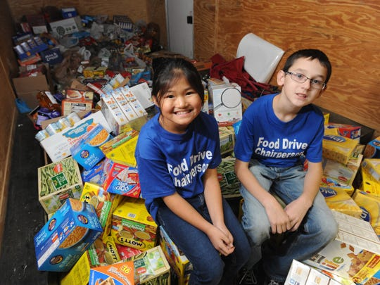 Corrine Woods, left, and Parker Manson sit inside a 1,000-cubic foot trailer with food they collected for Good Samaritan Food Pantry in December 2013. The pair collected about 5,000 pounds that year and 8,000 pounds in 2014.