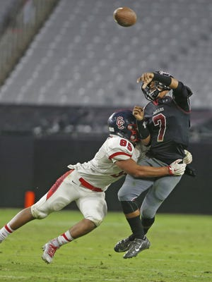 Desert Ridge's CJ Fowler (7) throws a pass while being hit by Centennial's Andrew Nichols (85) during the Division I State Championship game on Nov. 27, 2015 in Glendale, Ariz.