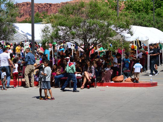 People gather under the shade of tents to eat and watch dancers perform at the Cinco de Mayo celebration Saturday, May 2, 2015. Those who couldn't find seats in the shade meandered around playing the many games offered during the event or sat where they could.