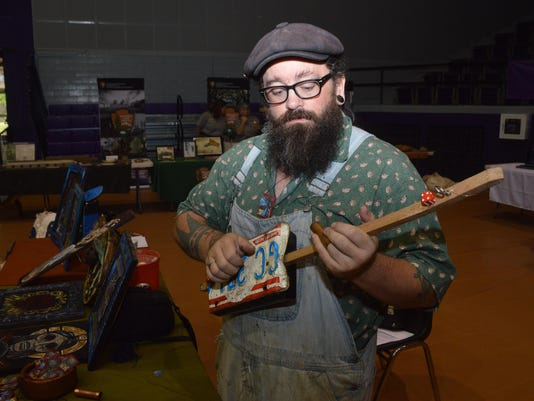 ANI NSU Folk Festival Gar Pickering who lives on Cane River strums a diddley bow he made from a license plate, a cigar box, dice and a tomato stake Saturday, July 19, 2014 at Prather Coliseum on the NSU campus. He makes diddley bows out of objects he finds